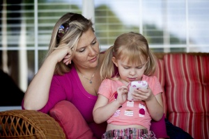 Renee Giroux-Nix's daughter, Bella, 3, plays games and uses educational apps on her mother's iPhone, in Cedar Park, Texas, Oct. 10, 2010. Just as adults have a hard time putting down their iPhones, so the device is now the Toy of Choice, akin to a treasured stuffed animal, for many 1-, 2- and 3-year-olds, a phenomenon that is attracting the attention and concern of some childhood development specialists. (Ben Sklar/The New York Times) -- PHOTO MOVED IN ADVANCE AND NOT FOR USE - ONLINE OR IN PRINT - BEFORE OCT. 17, 2010.